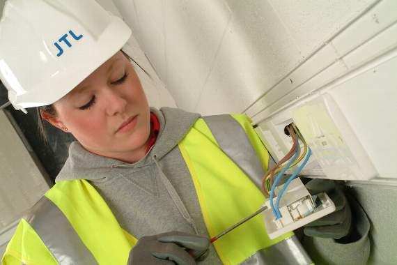 Young lady examining electrical wiring